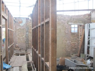 The stud walls creating a hallway leading to the utility room.