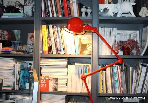 The oversized Anglepoise lamp is a spot of bright color against a perfectly layered bookshelf.