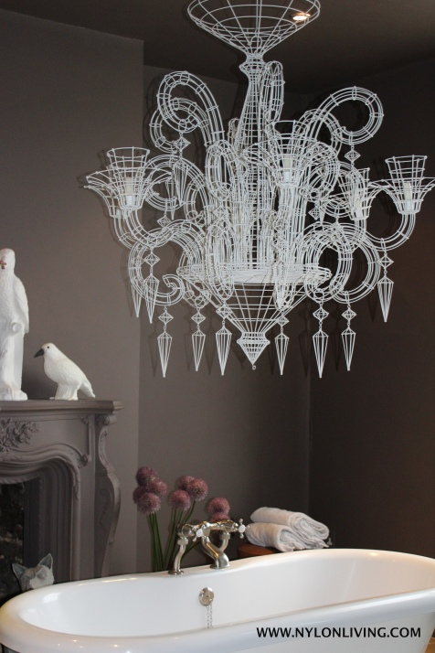 An oversized chandelier in the bathroom is an unexpected touch.